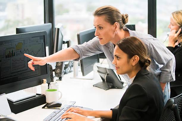 Businesswomen working together at computer workstation. stock photo