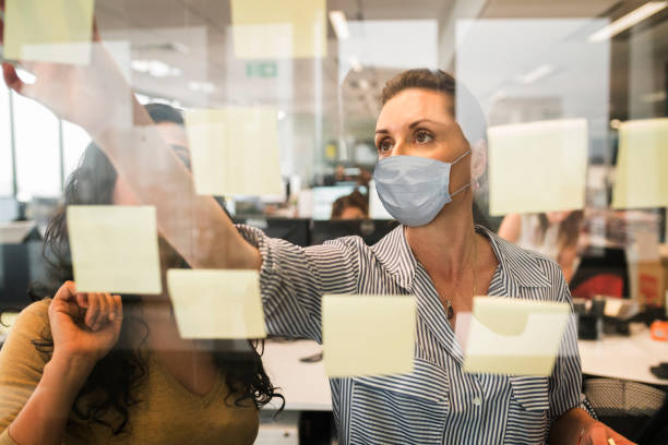 Businesswomen working together behind glass wall with reflections wearing mask. stock photo