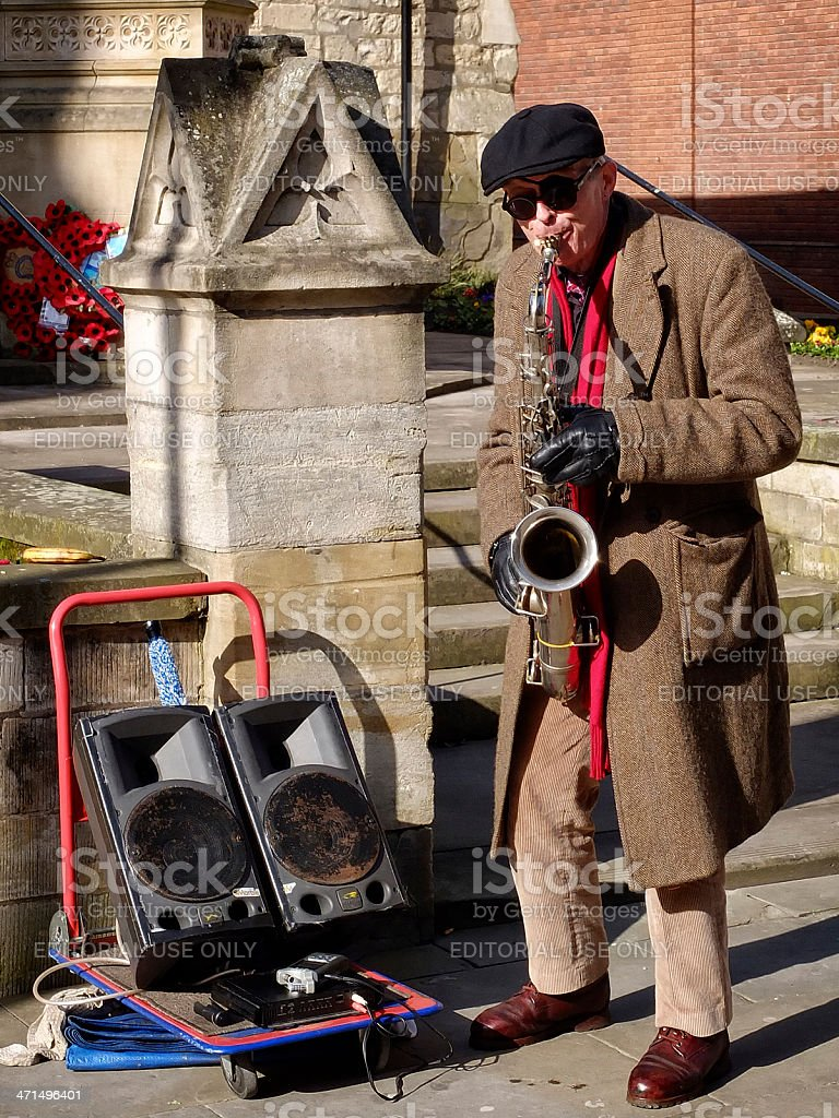 Busker playing a saxophone on Lincoln High Street, England royalty-free stock photo