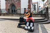 Funchal at Madeira, Portugal - August 01, 2014: Busker playing guitar downtown Funchal at Madeira Island, Portugal