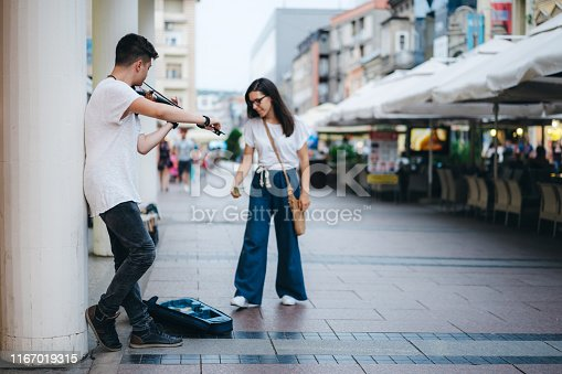 Young caucasian male busker playing a violin on city street and young woman putting money in his violin case.