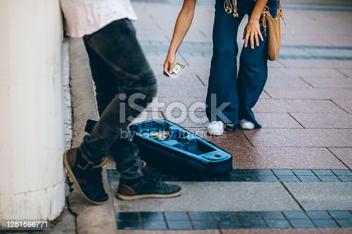 Young Caucasian busker playing violin on a street and a young cute woman giving him some money.