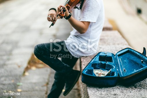 Young Caucasian man playing violin outdoor for money.