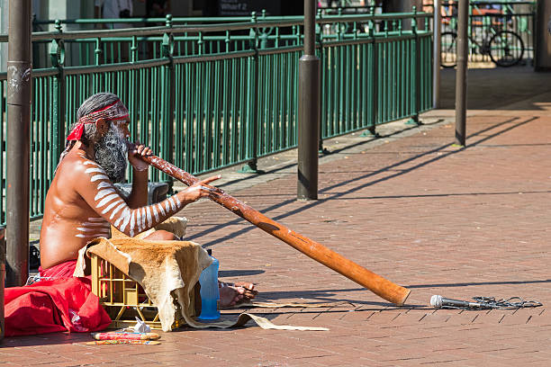 busker sitting and blowing didgeridoo, australian aboriginal musical instrument, australia - didgeridoo stock photos and pictures