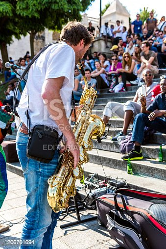 Paris, France - July 6, 2016: Busker with saxophone and people sitting on the stairs and listening to the busker front Sacre Couer Church at Paris, France.