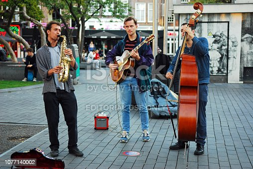 Three young street musicians playing jazz music on Rembrandt Square in the center of Amsterdam