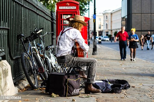 London, England - August 2, 2018: Street performer and an iconic British telephone booth