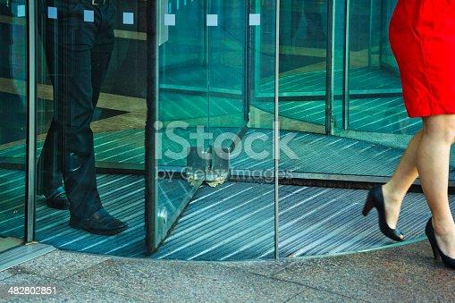 Business people walking through revolving door.