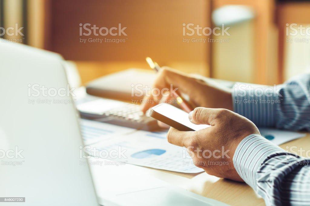 Busnessman à procura de dados de informações sobre smart phone sobre o mercado de ações e calcular na mesa no escritório. - foto de acervo