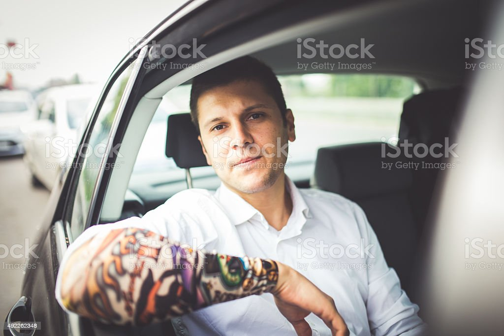 Bussines mam with tattoos in car stock photo