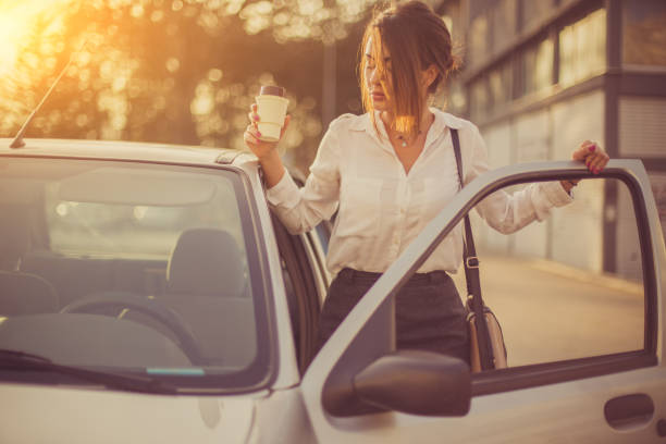 Bussines woman getting into car Businesswoman getting into car after coffee break entering stock pictures, royalty-free photos & images