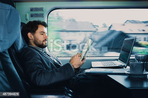 istock . bussinesman seating on a train  beside  window  and reading 487394626