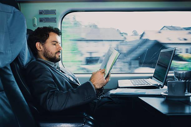 . bussinesman Sitzgelegenheiten auf einen Zug neben Fenster und lesen – Foto