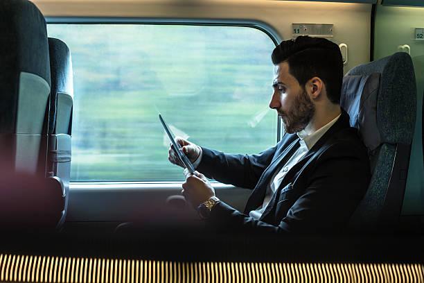 Bussinesman Sitzgelegenheiten auf einen Zug neben Fenster und Arbeiten – Foto
