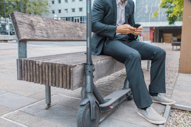 Bussinesman sitting on bench next to electric push scooter stock photo