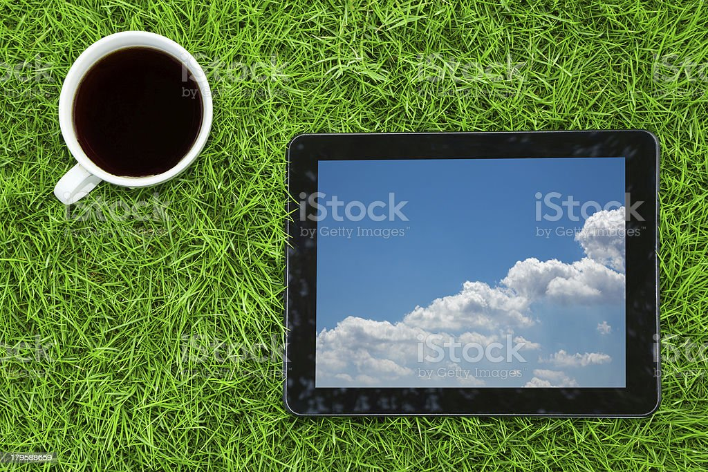bussiness growth:digital tablet and coffee on grass background royalty-free stock photo