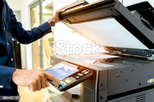 istock Bussiness man Hand press button on panel of printer, printer scanner laser office copy machine supplies start concept. 960462152