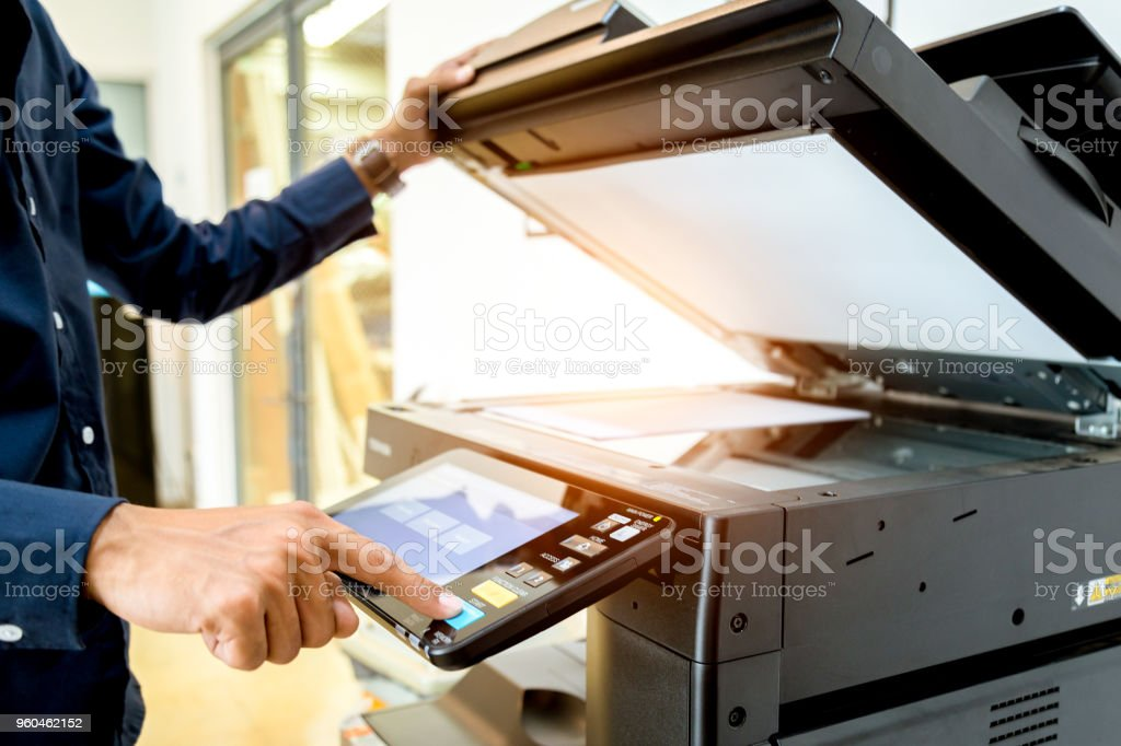 Bussiness man Hand press button on panel of printer, printer scanner laser office copy machine supplies start concept. stock photo
