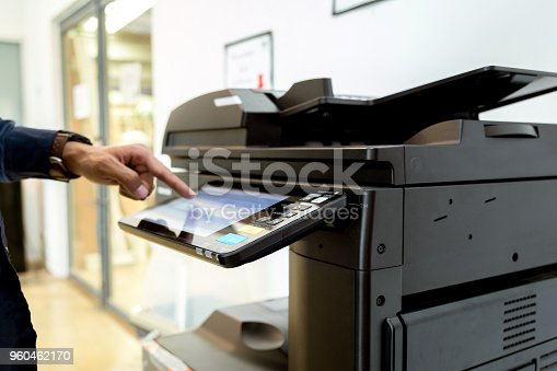 istock Bussiness man Hand press button on panel of printer, printer scanner laser office copy machine supplies start concept. 960462170