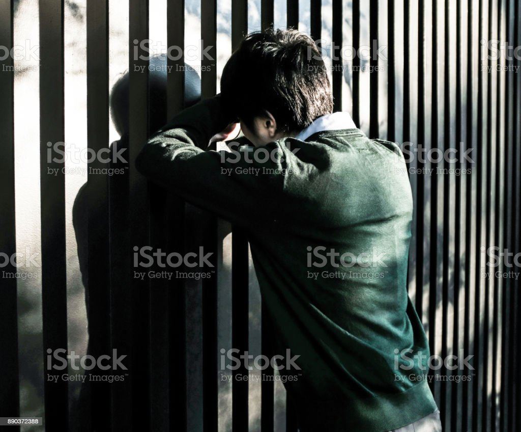 Bussinessman standing in front of a fence stock photo