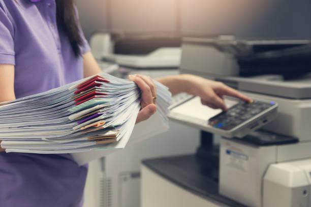 bussinesswoman met behulp van copier machine te kopiëren hoop papierwerk in het kantoor. - kopiëren stockfoto's en -beelden