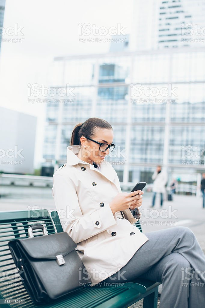 Bussineswoman sitting and using smart phone stock photo