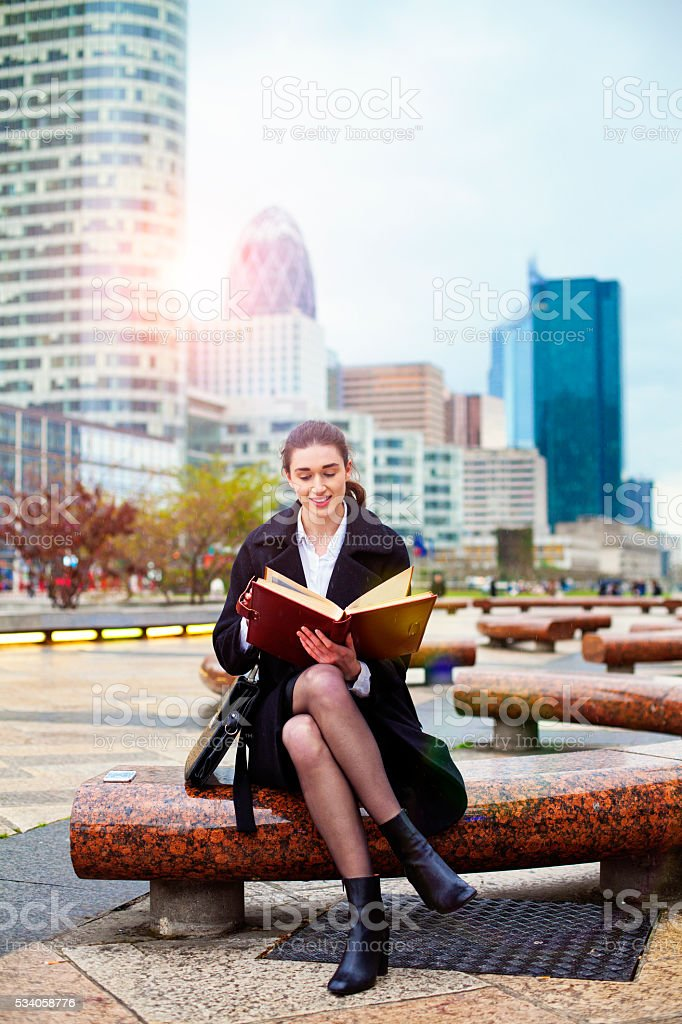 Bussineswoman sitting on bench and holding folder. stock photo