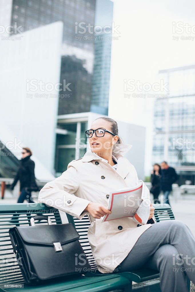 Bussineswoman sitting on bench and holding papers stock photo
