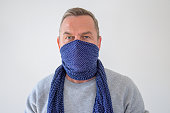 Bust portrait of middle-aged man in blue scarf wrap over his face, used as breathing mask for protection, standing against grey background and looking at camera