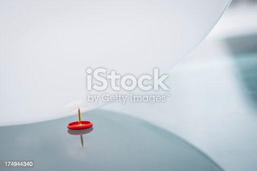A white ballon rolls over a red pin on a reflective glass table.
