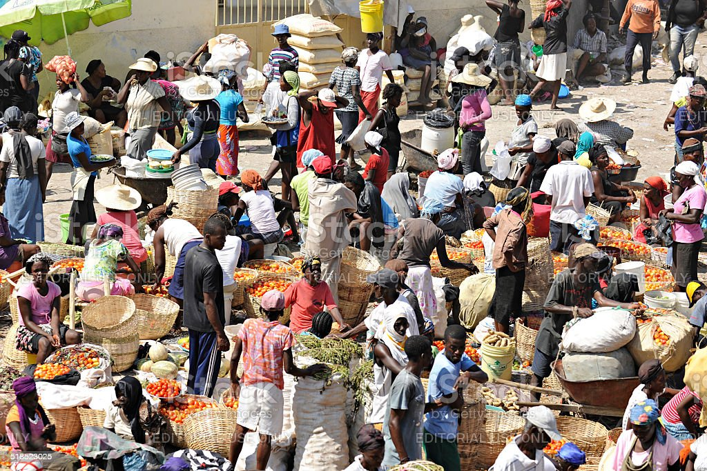 A crowd of Haitians buying and selling produce at an outdoor...