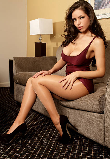 Busty Latina glamour model in tight maroon dress stock photo