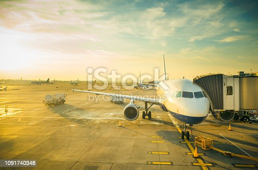 Passenger jet with attached air bridge on the apron, ready for logistics and boarding. Beautiful late afternoon/evening sunset image with great copy space.