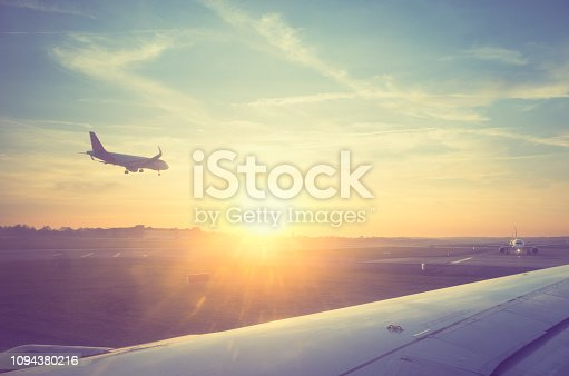 Passenger jet landing at sunset, shot from airplane queueing for takeoff at busy international airport. Beautiful late afternoon/evening sunset image with great copy space.