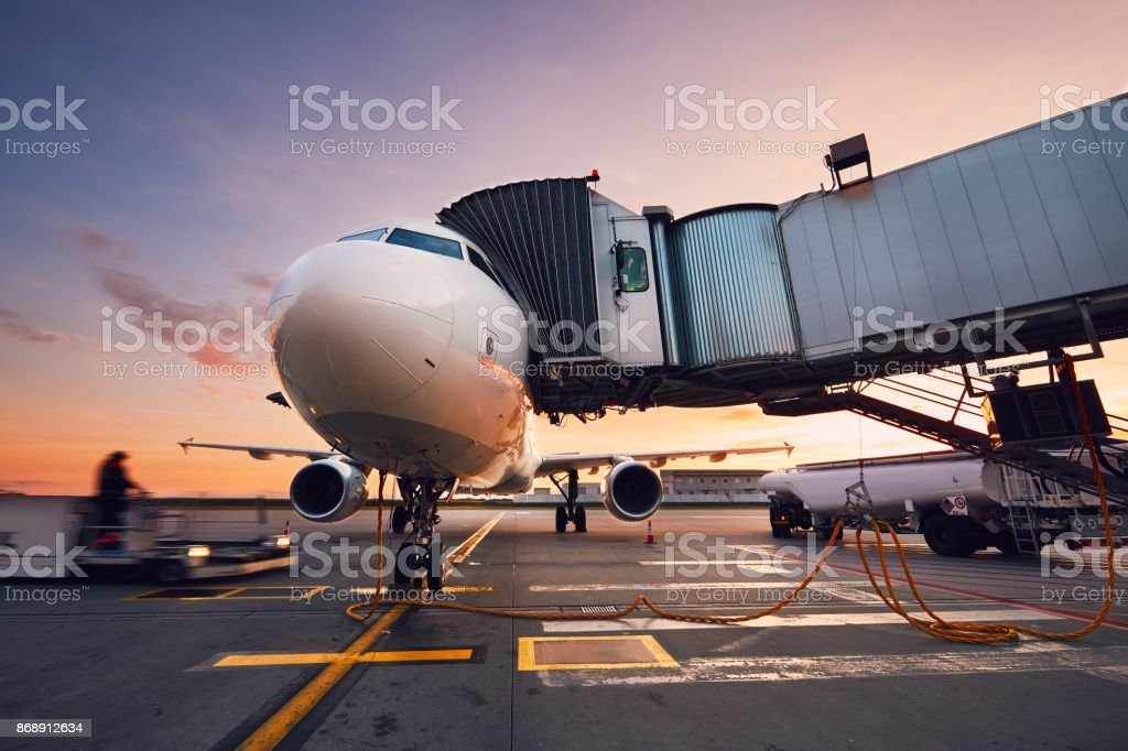 Busy airport at the colorful sunset stock photo