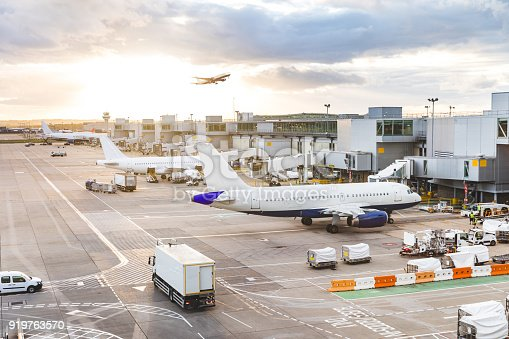 Busy airport view with airplanes and service vehicles at sunset. London airport with aircrafts at gates and taking off, trucks all around and sun setting on background. Travel and industry concepts