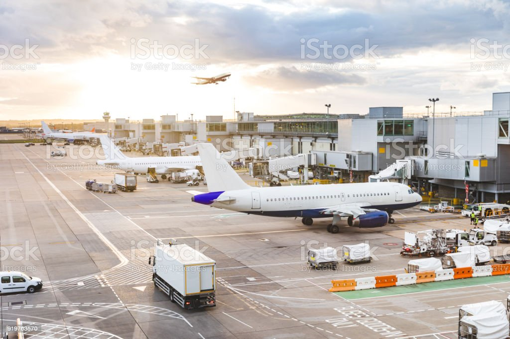 Busy airport view with airplanes and service vehicles at sunset - foto stock