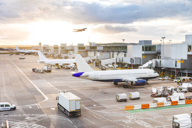 busy airport view with airplanes and service vehicles at sunset - airport stock photos and pictures