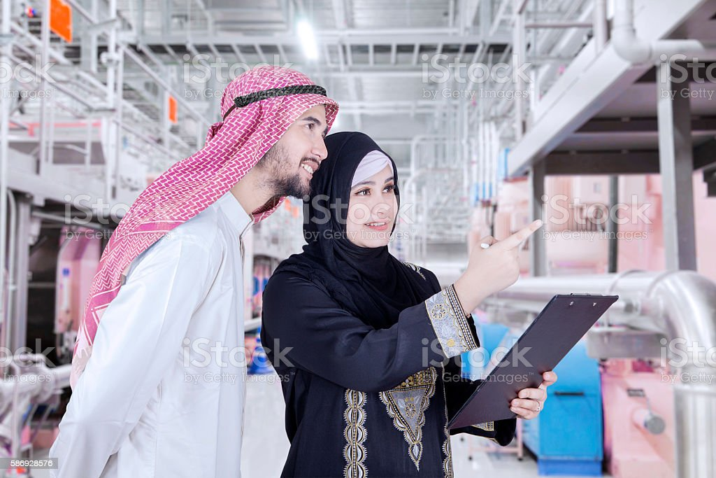Busy Arabian businesspeople in the factory stock photo
