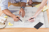Male and female architects use pencils and a ruler as they work on a blueprint together. Crumpled pieces of paper and a smart phone or calculator is on the table.