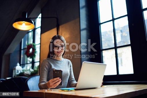 istock Busy attractive business woman in glasses checking email box via smartphone 693210316