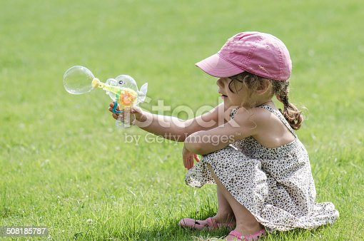 A little girl blowing soap bubble using a toy gun while being seated on the grass