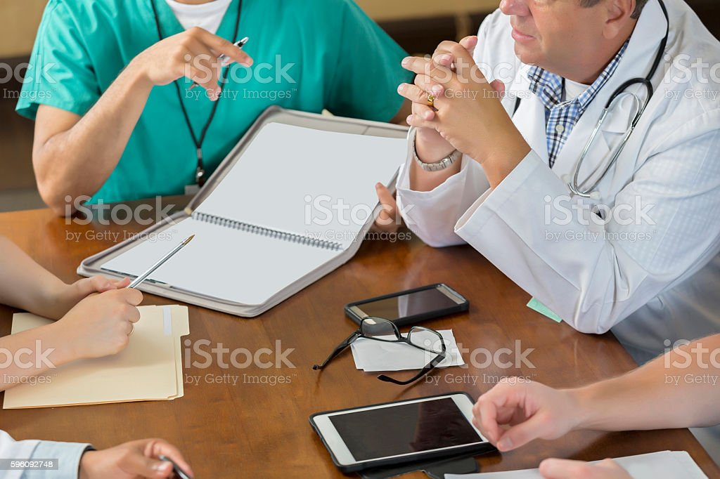 Busy board room table during hospital staff meeting royalty-free stock photo