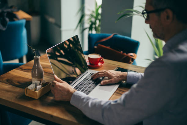 busy business coffee break businessman using laptop on coffee break in cafe bar old man working in a pub stock pictures, royalty-free photos & images