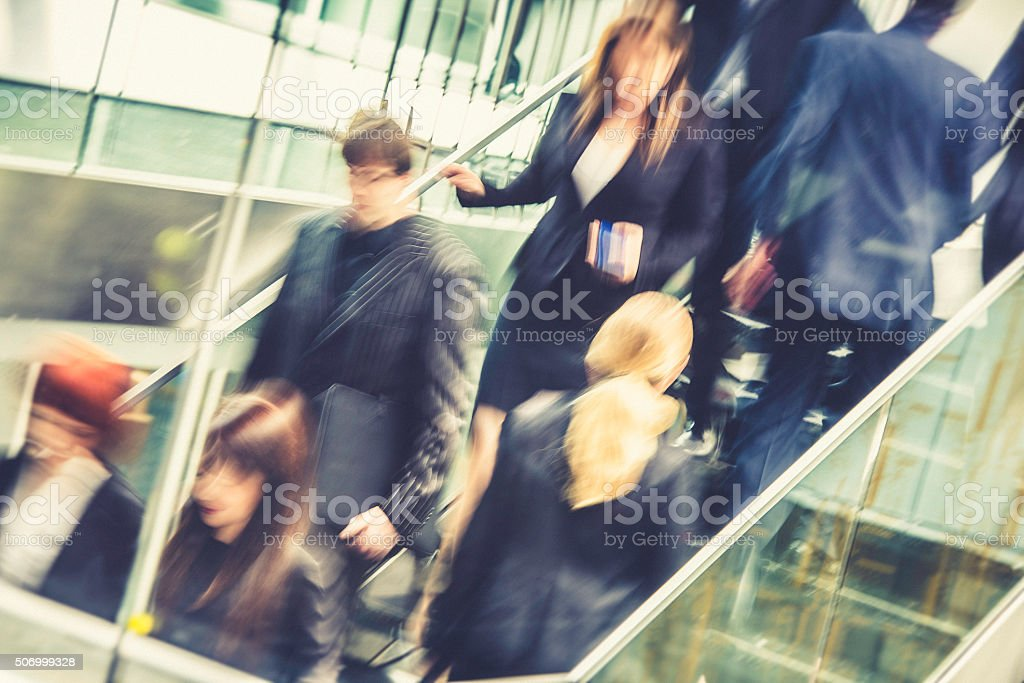 Busy business people rushing up and down the staircase stock photo