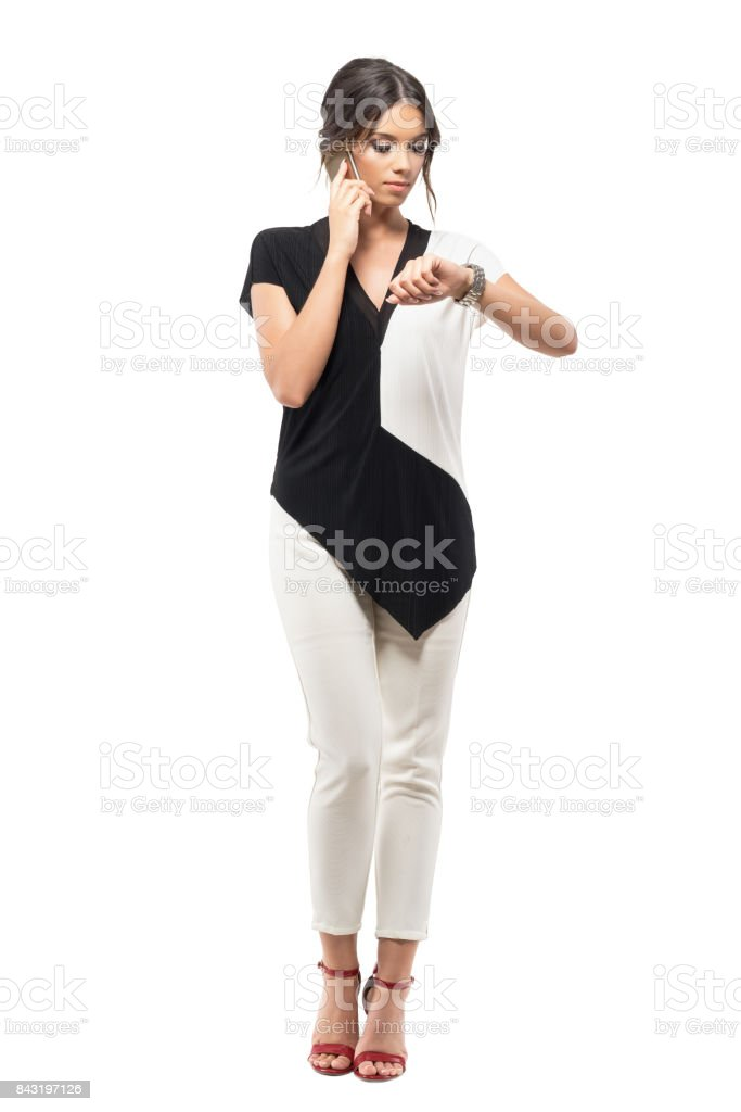 Busy business woman checking time on wrist watch talking on the mobile phone. stock photo