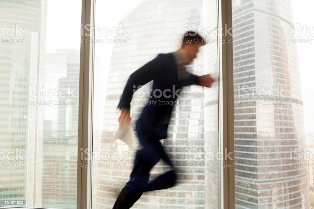 Homme d'affaires bien remplie se hâtant vers le haut, fait tard, vue sur la ville, flou de mouvement - Photo