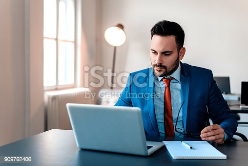 Busy businessman in office working on laptop.
