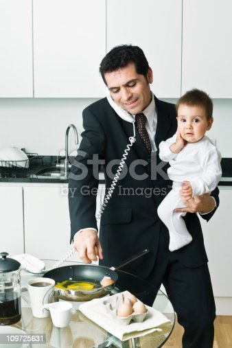 istock Busy Businessman Making Breakfast and Holding Baby 109725631