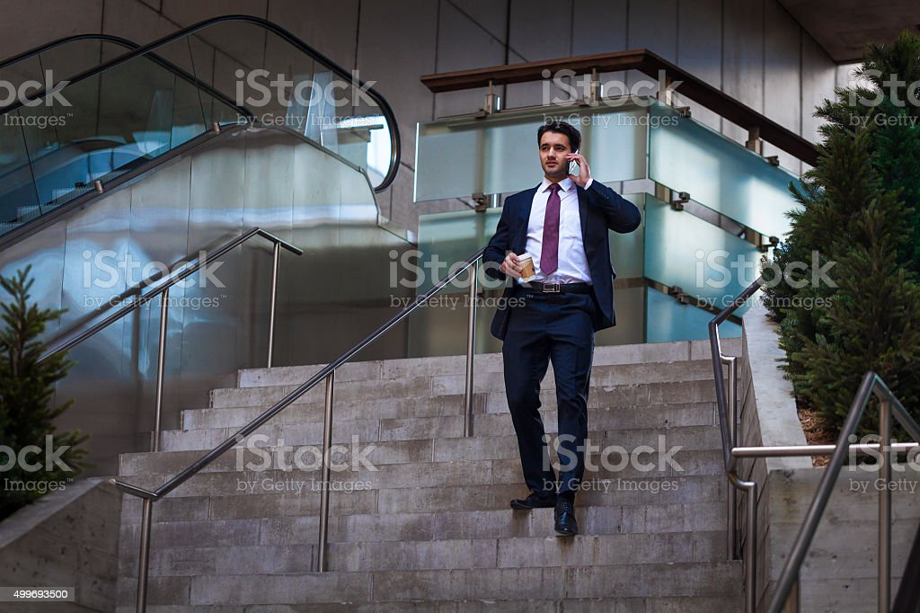 Busy businessman on stairs stock photo
